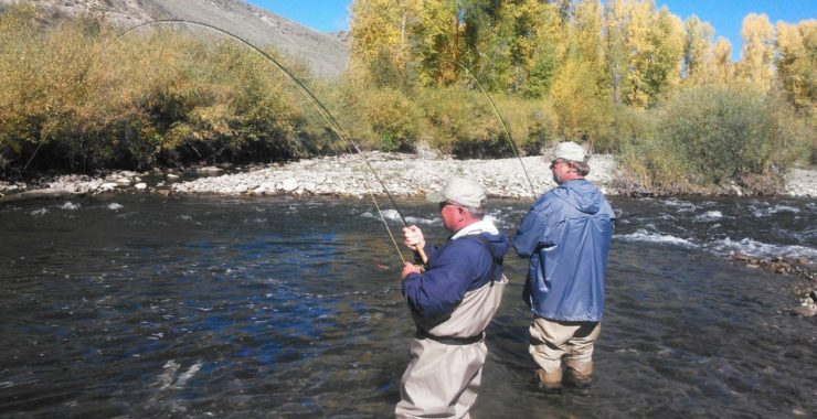 Image showing two elder fishermen fishing on the river bank