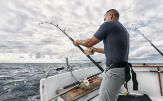 A man trolling his fishing rod from a motor boat