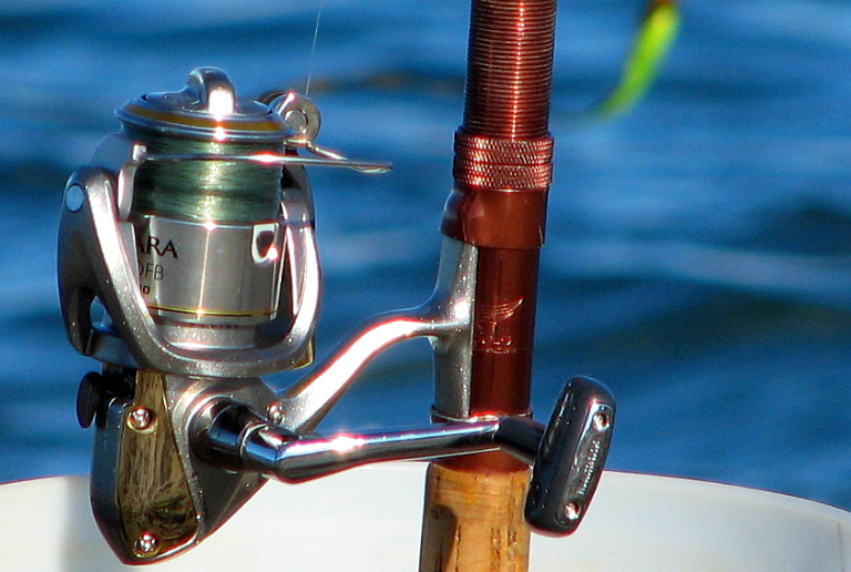 A Close-up View Of Fishing Rod & Gear In A Sea Background.