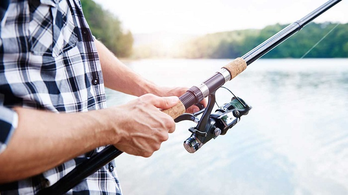 On A Sunny Day, A Man Holding The Fishing Rod For Fishing.