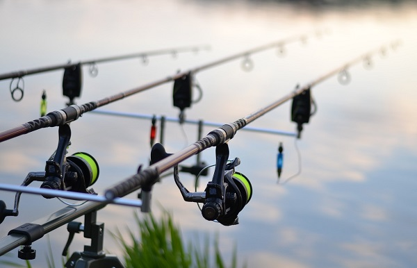 Three Fishing Rods With Professional Reel Set Up On The Lake.