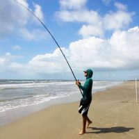 Man Casting A Fishing Line Into surf