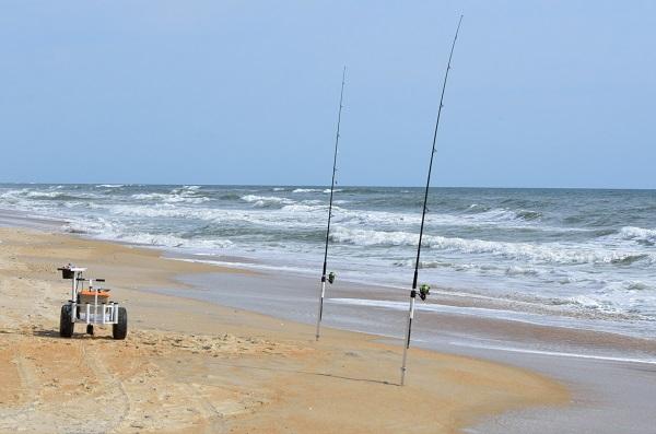 Fishing Rods Set Up On Beach Shore.