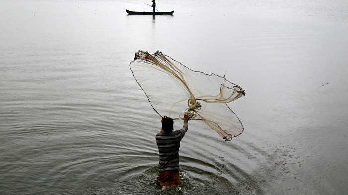 A Man Throwing The Net Over The Water.